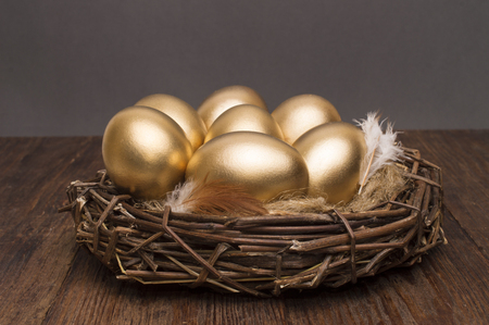 Nest with golden eggs on a wooden background. The concept of successful retirement