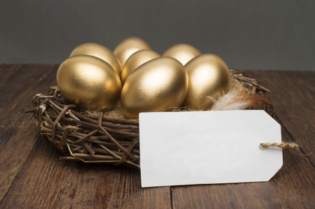 Nest with golden eggs with a tag and place for text on a wooden background. The concept of successful retirement