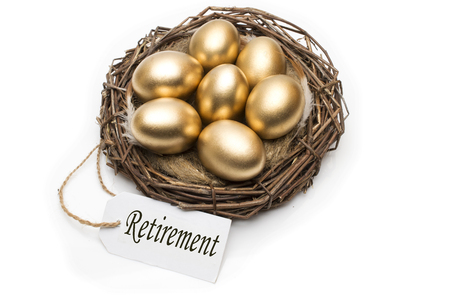 Nest with golden eggs with a tag and a word retirement on a white background. The concept of successful retirement