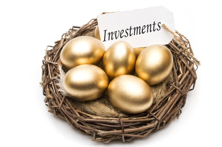 Nest with golden eggs with a tag and a word of investments on a white background. The concept of successful retirement. Stock fotó