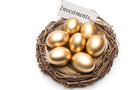 Nest with golden eggs with a tag and a word of investments on a white background. The concept of successful retirement