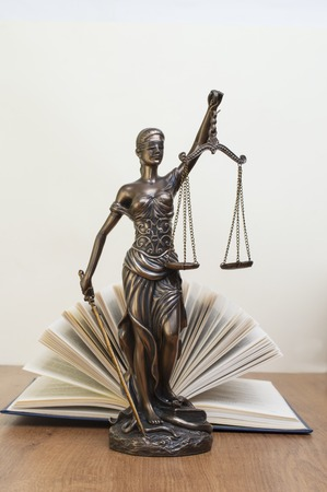 statue of justice on wooden table against the background of an open book 写真素材