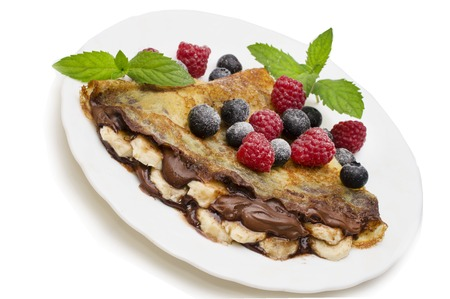 Homemade crepes served with chocolate cream, fresh blueberries and raspberries, powdered sugar on a white background Stock Photo