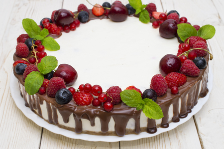 Delicious tart with fresh strawberries, raspberries and cherry on the table