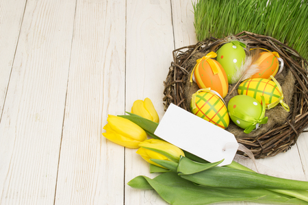 Easter decoration with eggs and tulips on a wooden background. Reklamní fotografie
