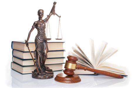 statue of justice, judges hammer behind books on a white background Reklamní fotografie