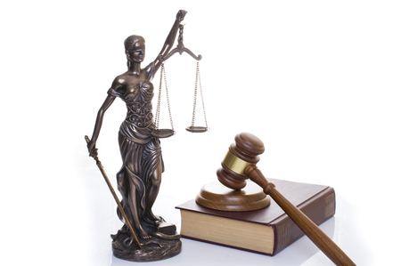 statue of justice, judges hammer behind books on a white background