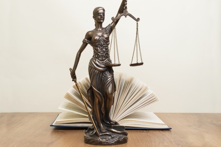statue of justice on wooden table against the background of an open book Reklamní fotografie