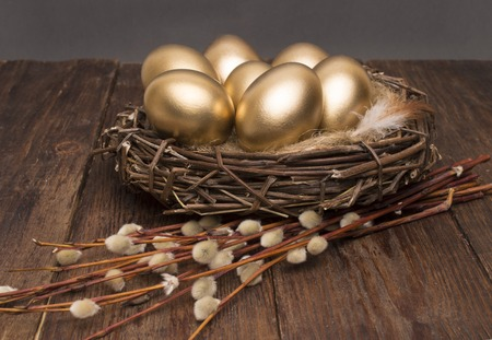 Nest with golden eggs with willow on a wooden background. Easter.