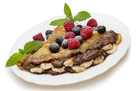 Homemade crepes served with chocolate cream, fresh blueberries and raspberries, powdered sugar on a white background Reklamní fotografie