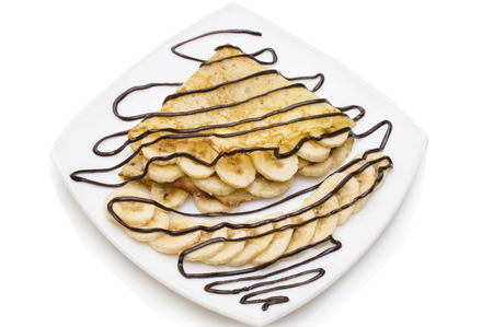 Crepes with chocolate cream and banana on white background.