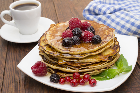 Delicious pancakes with berries and maple syrup. Top