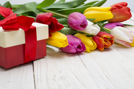 bouquet of tulips with a gift on rustic wooden board Reklamní fotografie