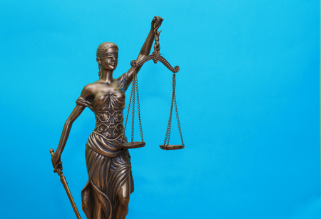 statue of justice on wooden table against the background of an open book. Stock Photo