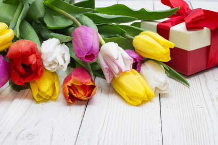 bouquet of tulips with a gift on rustic wooden board 스톡 콘텐츠