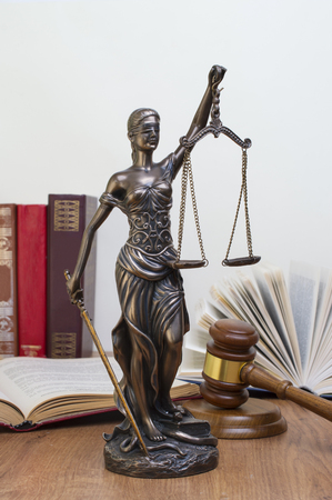 statue of justice on wooden table against the background of an open book.