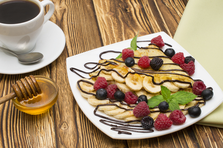 Homemade crepes served with chocolate cream, Banana, fresh blueberries, raspberries on a wooden background, pancakes. 스톡 콘텐츠
