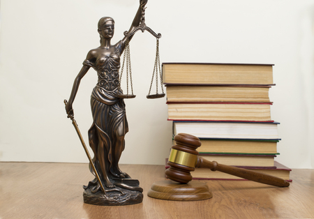 statue of justice, judges hammer behind books on a wooden table