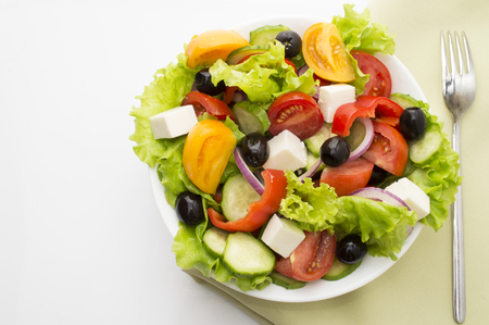 fresh vegetable salad isolated on white background with tomatoes, black olives and greens close 스톡 콘텐츠
