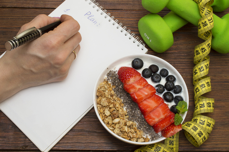 Workout and fitness dieting copy space diary. Dumbbell, vegetable smoothies and measuring tape on rustic wooden table Imagens