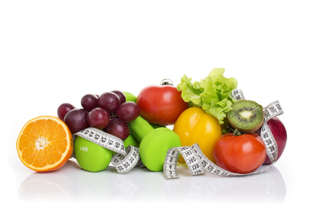 fitness equipment and healthy food isolated on white. apple, pepper, grapes, kiwi, orange, dumbbells and measuring tape. Imagens