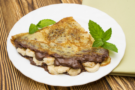 Crepes with bananas and cream on a wooden background
