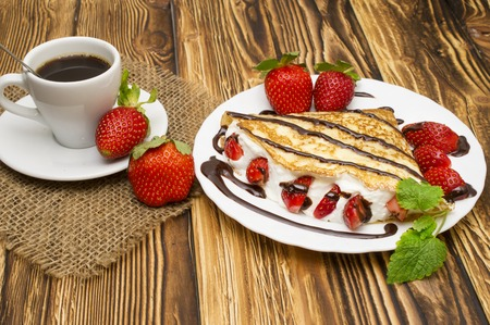 Crepes with Banana, Chocolate and strawberries on a wooden background, pancakes. Imagens