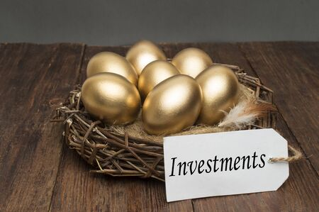 Nest with golden eggs with a tag and a word of investments on a wooden background. The concept of successful retirement Stock fotó