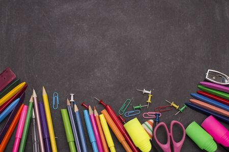 School supplies on blackboard background ready for your design.