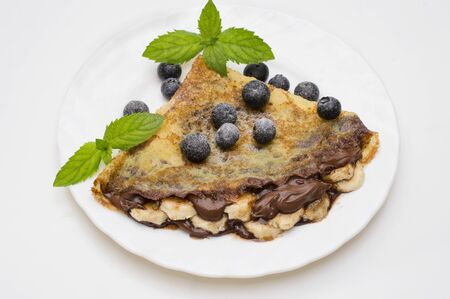 homemade crepes with chocolate cream, banana and blueberries on white background. pancakes 스톡 콘텐츠