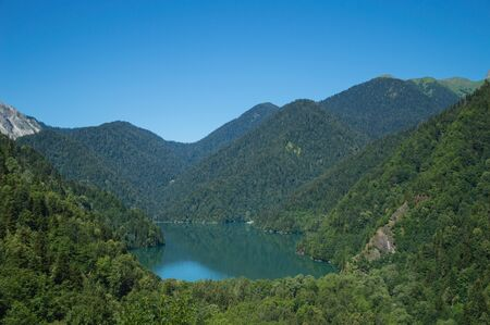 Panoramic view on mountain lake in front of mountain range. 스톡 콘텐츠 - 129700909