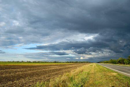 empty road: empty road near field. Landscape Stock Photo
