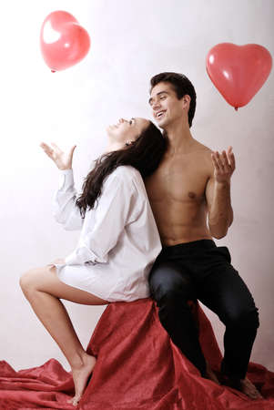 beautiful young couple with red hearts photo