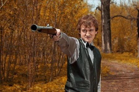 トリガー: 男は銃の引き金を引きます。屋外撮影