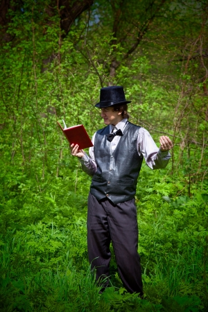 man reading book in old style dress. outdoor shot Stock Photo