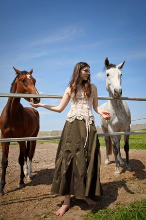 portraite of attractive girl and horses. outdoor shot photo