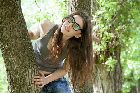 hands behind head: attractive girl in glasses. outdoor shot Stock Photo