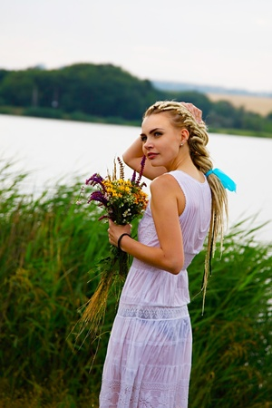 wet clothes: attractive girl in wet dress with flowers in hands. outdoor shot