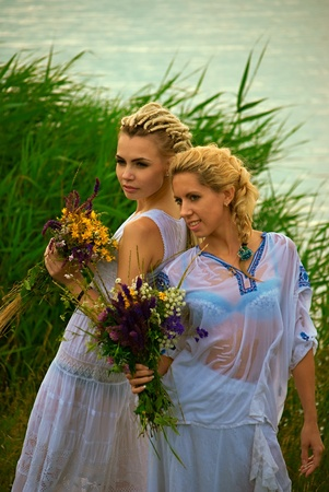 wet clothes: two girls with wildflowers in wet clothing. outdoor shot