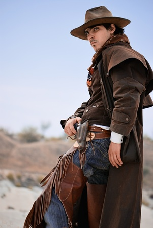 specific clothing: handsome cowboy in specific clothing with weapon. outdoor shot