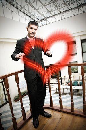 indoor shot: hombre guapo dando coraz�n rojo. tiro bajo techo
