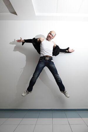 indoor shot: feliz saltando hombre guapo. tiro bajo techo