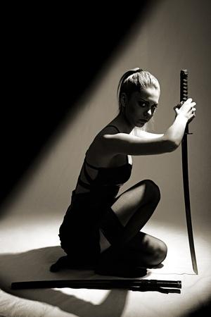 portrait of serious girl with katana. studio shot