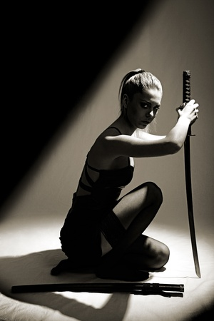 katana: portret van ernstig meisje met katana. studio-opname