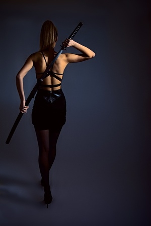 portrait of serious girl with katana. studio shot