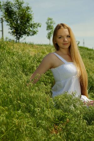 attractive girl sitting on spring meadow. outdoor shot photo
