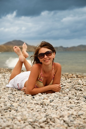 girl in glasses on the shore and smiling photo