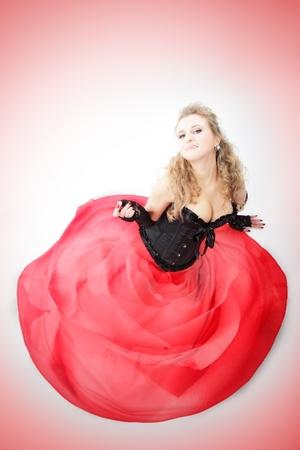 sitting woman in red skirt. studio shot photo