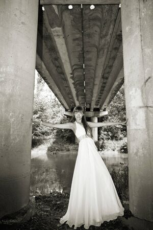 attractive girl standing under bridge. olutdoor shot photo