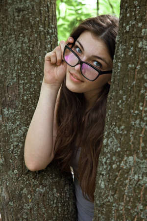 attractive girl holds the hand eyeglasses. outdoor shot photo